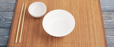 Two white empty bowl and two wooden chopsticks lie on a bamboo mat that sits on a wooden table made of textured boards.