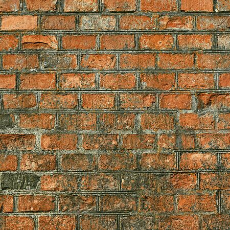 The wall is made of old orange bricks, the masonry is uneven