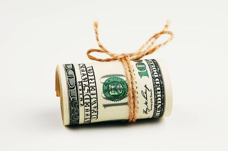 Isolated roll of dollars. A large roll of hundred-dollar bills lies on a white background in the middle of the image, tied with a rope. Close up. Full-contrast color image. with space for text labels. Stock Photo