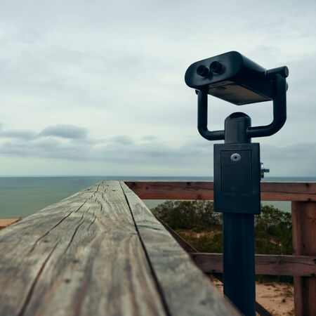Binoculars for the observation deck on the beach at the wooden railing.