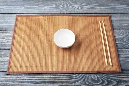 A white empty bowl and two wooden chopsticks lie on a bamboo mat that sits on a wooden table made of textured boards.