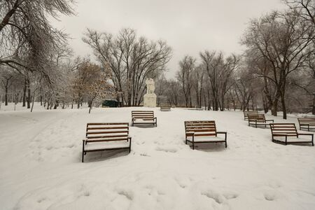 Winter landscape, Park benches covered with snow, after a heavy snowfall. The snow on the branches of trees and large drifts. Foto de archivo