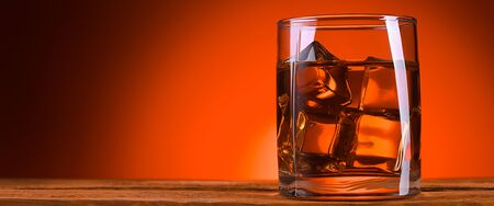 A glass of whiskey or cognac and ice cubes, close-up on a wooden table. Bright orange brown luminous background. Foto de archivo