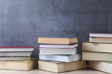 Stacks of books several on a gray background close-up. Hardcover books in different colors. At the top there is a free space for the inscription, text. Back to school, education, learning,