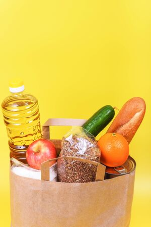 Paper bag with food supplies for the period of quarantine isolation on a yellow background. Delivery, donation, coronavirus. Copyspace. Buckwheat pasta sugar peas canned food tomatoes cucumber bread orange apples eggs ginger.