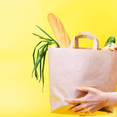Paper bag with food supplies for the period of quarantine isolation on a yellow background.