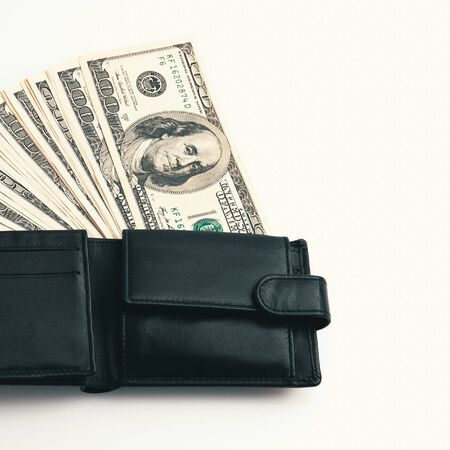 A black wallet with dollars in it on a white background. The hundred-dollar bills are half out and arranged in a fan. Full-contrast color image.