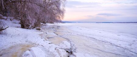 Winter landscape at dawn, riverbank of a frozen ice. Hanging tree branches, beautiful sky, large ice floes.