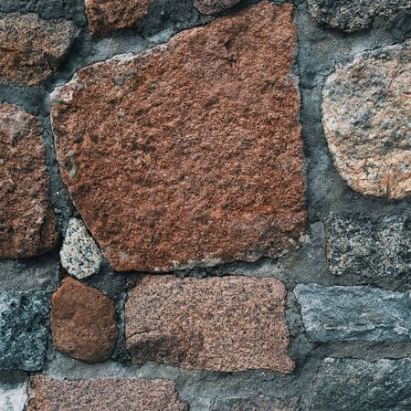 Background of old stone wall with stones of different sizes and colors