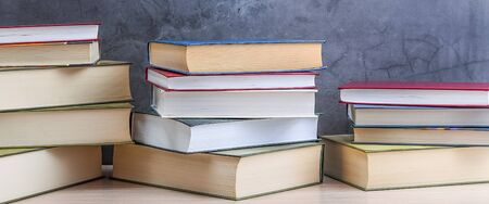 Stacks of books several on a gray background close-up. Hardcover books in different colors. At the top there is a free space for the inscription, text, and logo. Back to school, education, learning,