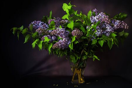 bouquet of beautiful spring lilac flowers on a table on a dark background