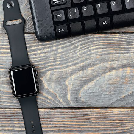 Workplace smart watch, keyboard, mouse, all black, brutal accessories, on a table made of textured boards with free space for lettering, text and logo. smart watch, keyboard, mouse on a wooden table.
