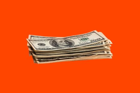 Isolated bundle of dollars. A large stack of hundred-dollar bills sits on an orange background in the middle of the image. Close up. Full-contrast color image. with space for text labels. Foto de archivo