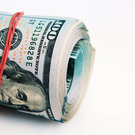 Isolated roll of dollars. A large roll of hundred-dollar bills lies on a white background on the right of the image. Close up. Full-contrast color image with space for text labels.