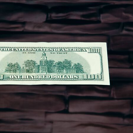 A hundred-dollar bill. Close-up, against a brick wall of dark red brown color. Full-contrast color image. Free space for the logo and text label. Foto de archivo
