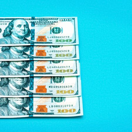 A row of one hundred American dollar bills in close-up against a blue background. Close-up, full-contrast color image. Free space for labels and text.