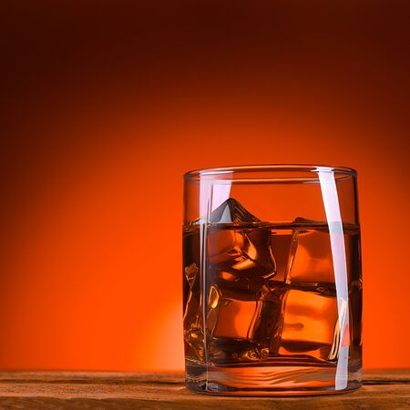 A glass of whiskey or cognac and ice cubes, close-up on a wooden table. Bright orange brown luminous background. Space for lettering, text, and logo. Layout for advertising. Brutal view.