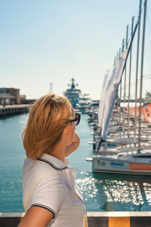 A blonde girl looks at the sea and yachts. She is wearing glasses and a white t-shirt, a view from the back.