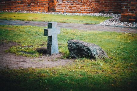 An ancient stone funeral cross and a tombstone on the burial ground near the wall of the old castle. Reklamní fotografie
