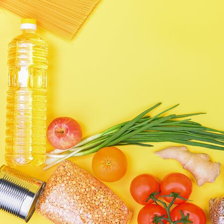 Food delivery, donation, food supply, copyspace. On a yellow background, buckwheat, pasta, sugar, peas, canned food, tomatoes, cucumber bread orange apple eggs ginger package coronavirus quarantine Reklamní fotografie