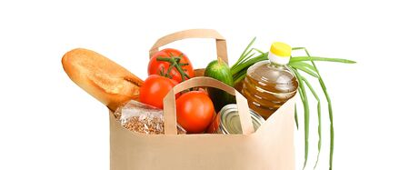 Paper bag with food supplies for the period of quarantine isolation on a white background. Delivery, donation, coronavirus. Copyspace. Buckwheat pasta sugar peas canned food tomatoes cucumber bread orange apples eggs ginger.