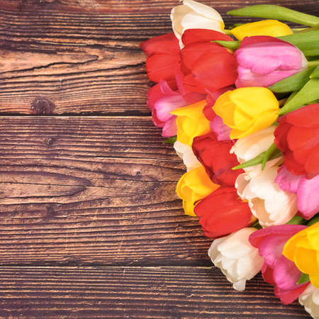 Large bright bouquet of multi-colored tulips on wooden boards of dark brown color
