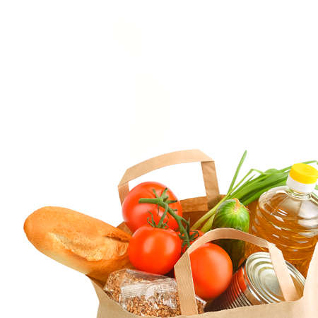 Paper bag with food supplies for the period of quarantine isolation on a white background. Copyspace.