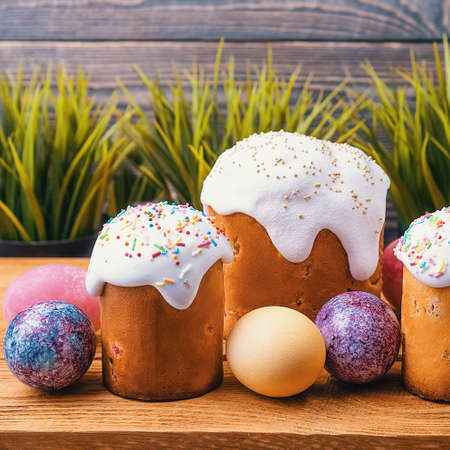 Easter cakes and Easter colored eggs on a wooden background.