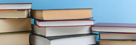 Stacks of books several on a blue background close-up. Back to school, education, learning, 版權商用圖片
