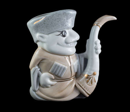 domestic staff: ceramic figurine Georgian man who holds the horn isolated on black