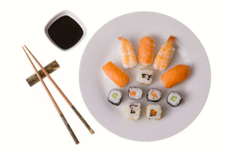 Variety of sushi rolls: Nigiri Sushi salmon and king prawn; California rolls and Makizushi. Soy sauce and chopsticks. Isolated on white photo