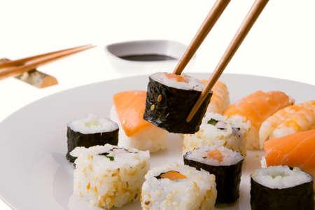 Choosing a sushi rolls from variety of Nigiri Sushi salmon and king prawn, California rolls and Makizushi rolls photo