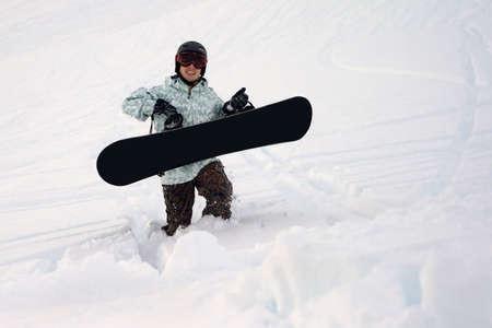 deep powder snow: Snowboarder walking through deep powder snow