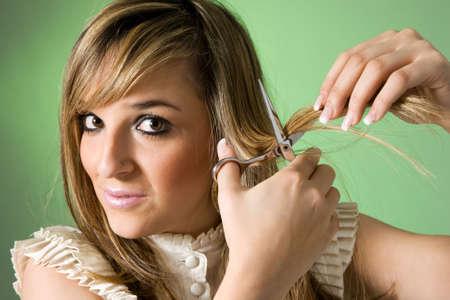 haircutting: Young women cutting her hair. Studio shot