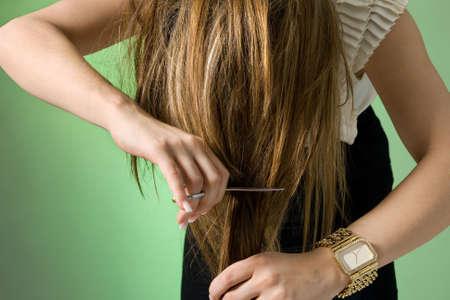 Young women cutting her hair. Studio shot Stock Photo - 6938252