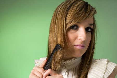 Young women combing her hair. Studio shot photo