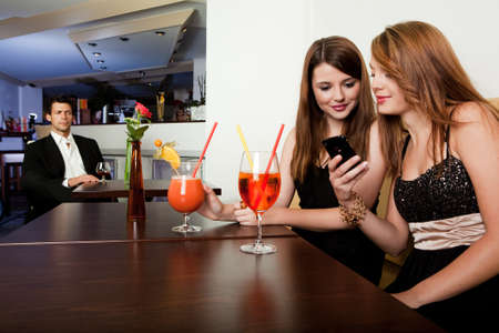 female bonding: Showing cool stuff on a mobile phone Stock Photo