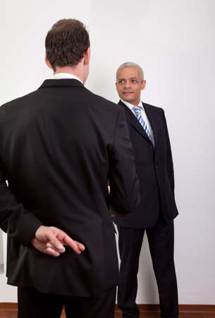implausible: Crossed Fingers At Handshake Stock Photo