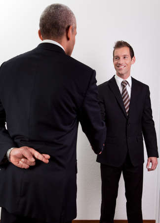 deceit: Crossed Fingers At Handshake Stock Photo