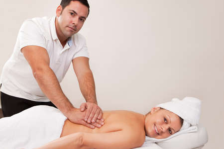 Young beautiful woman getting back massage photo