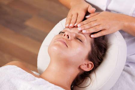Young beautiful woman getting facial massage photo