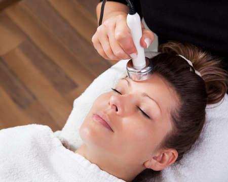 tratamiento facial: Joven mujer recibiendo la terapia con l�ser Foto de archivo