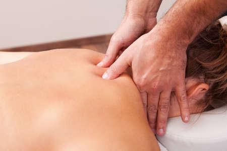 adjustment: Young beautiful woman getting back massage