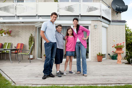 Caucasian mother and father with children standing in front of house photo