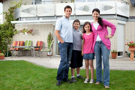 Portrait of happy young family standing in front of their house