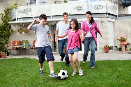 jugando futbol: Cute niños jugando al fútbol con sus padres en el patio trasero