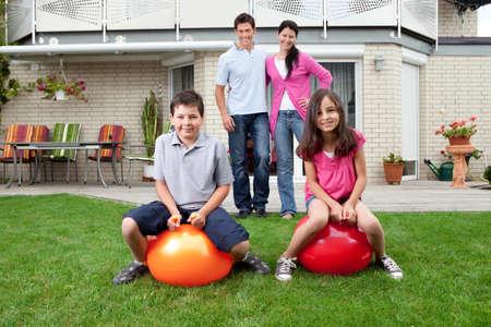 hermanos jugando: Retrato de la madre el padre y los ni�os en su patio trasero