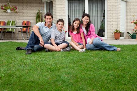 Caucasian family portrait sitzt vor ihrem Haus lächelnd