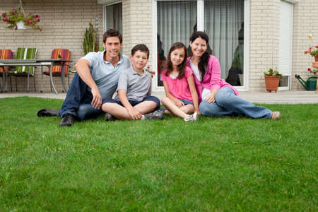 Portrait de famille caucasienne assis en face de leur maison souriante