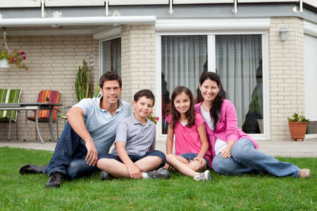 backyard woman: Portrait of happy family of four sitting in backyard of new home